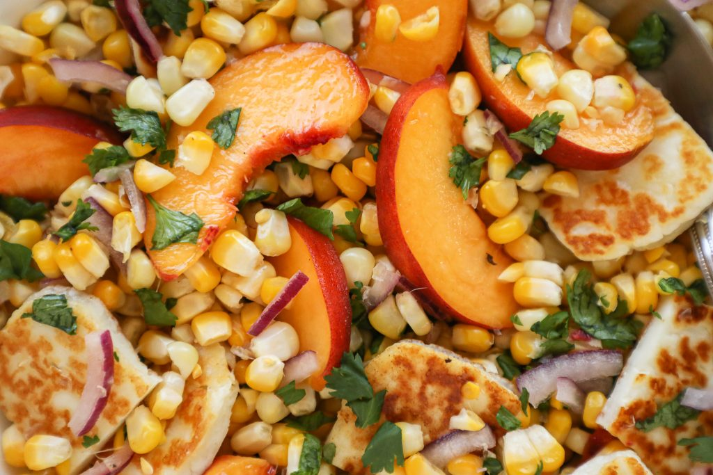 Peaches, halloumi cheese, fresh corn, red onion and cilantro are all tossed in lime juice and honey to make this delicious salad!