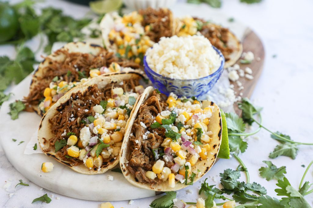 Easy Mexican pulled pork that are perfect for tacos, salads and even nachos too! Plus they go great with my homemade zesty corn salsa!