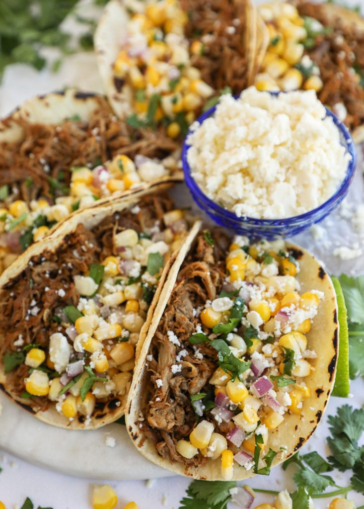 An easy Mexican pulled pork recipe that's cooked in the crock pot with lots of herbs and spies and then served with an easy Mexican corn salsa! This recipe comes out perfectly moist and tender every single time!