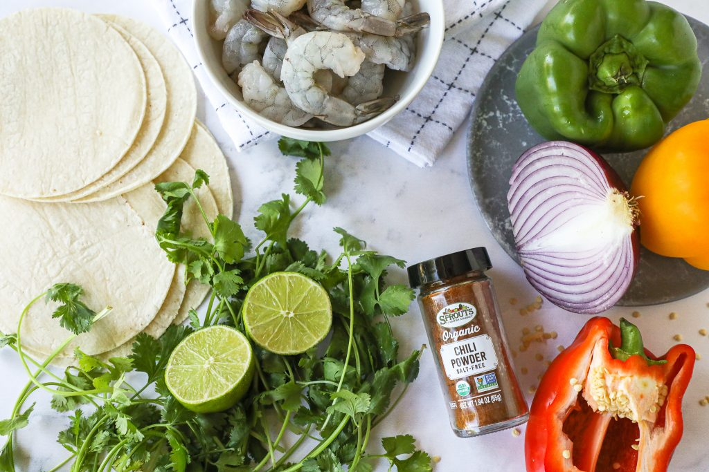 Easy sheet pan fajitas with only 4 ingredients! All you need is raw shrimp, bell peppers, onion and your favorite fajita seasoning!