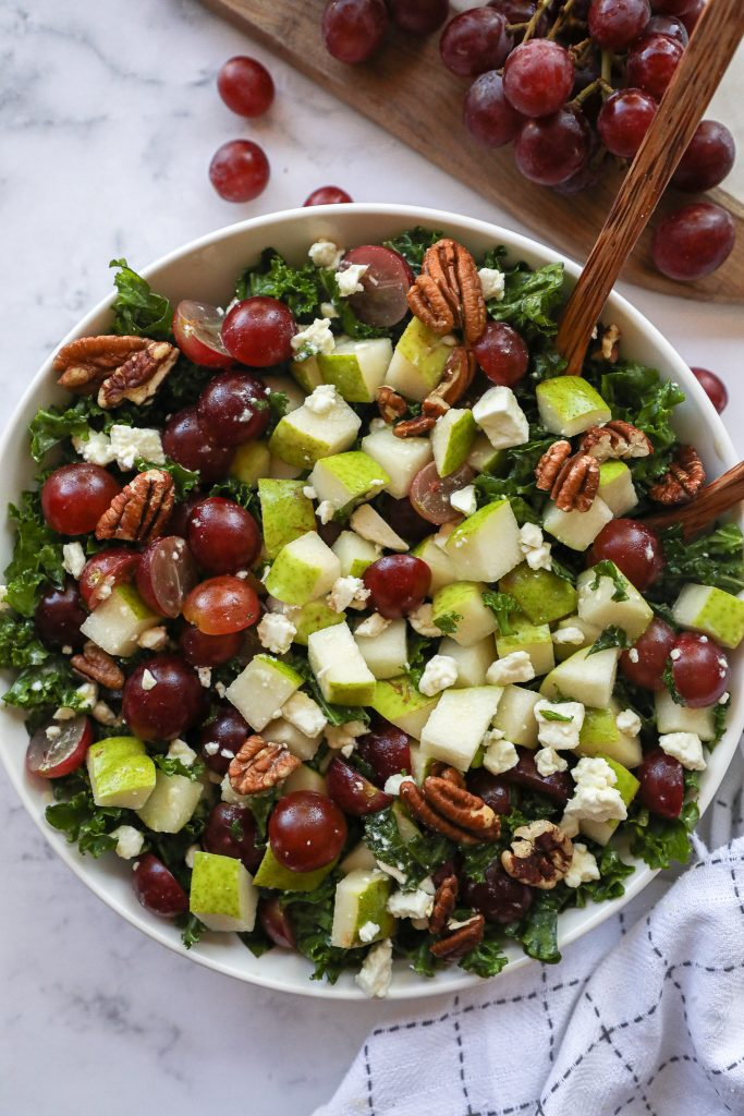 Fresh bartlett pears, red grapes, feta cheese and toasted pecans are all tossed with tender kale in a sweet maple vinaigrette!It's such a refreshing side dish!