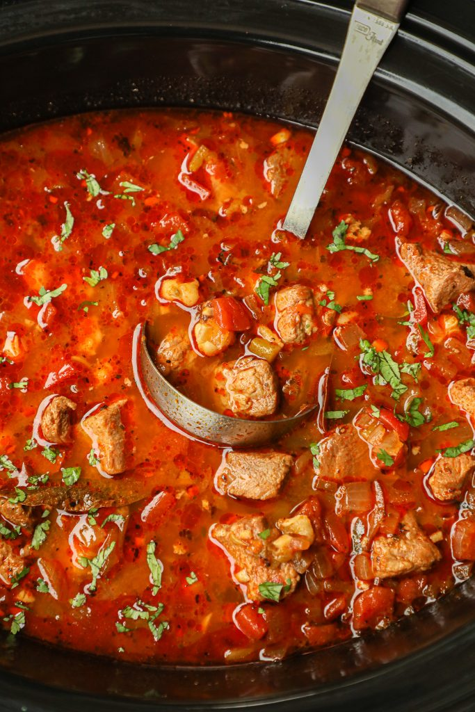 An easy slow cooker recipe that's loaded with shredded pork, hominy and spicy Mexican flavors! It's cozy comfort food at it's finest!