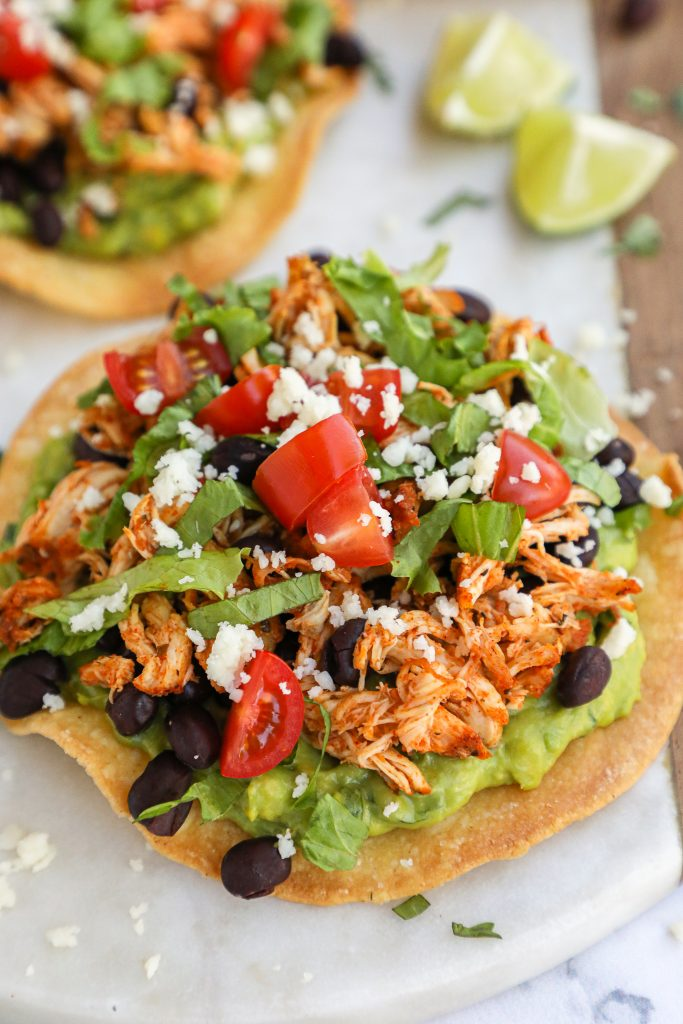 Close up picture of a spicy chicken tostada with black beans, tomatoes, lettuce, cotija cheese and guacamole sitting on a marble board served with lime wedges