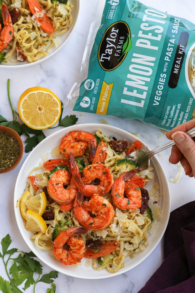 A delicious 10 minute meal made with pesto pasta, sauteed shrimp, fresh seasonal veggies and a sprinkle of parmesan cheese! It's fast, healthy and so easy to make!
