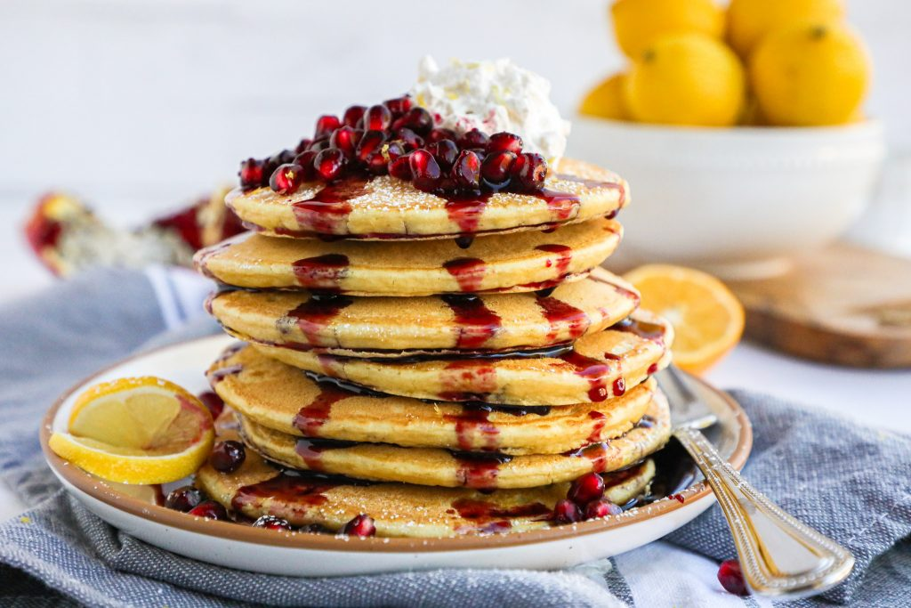 Healthier pancakes with a holiday spin! These lemon ricotta pancakes are drizzled with a sweet pomegrante syurp and topped with fresh pomegranates and whipped cream!