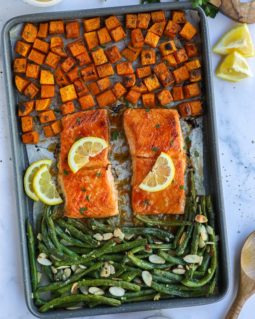 Sweet and tangy maple mustard salmon filets, crispy butternut squash and garlic and almond green beans all roasted on one pan for a delicious winter meal!