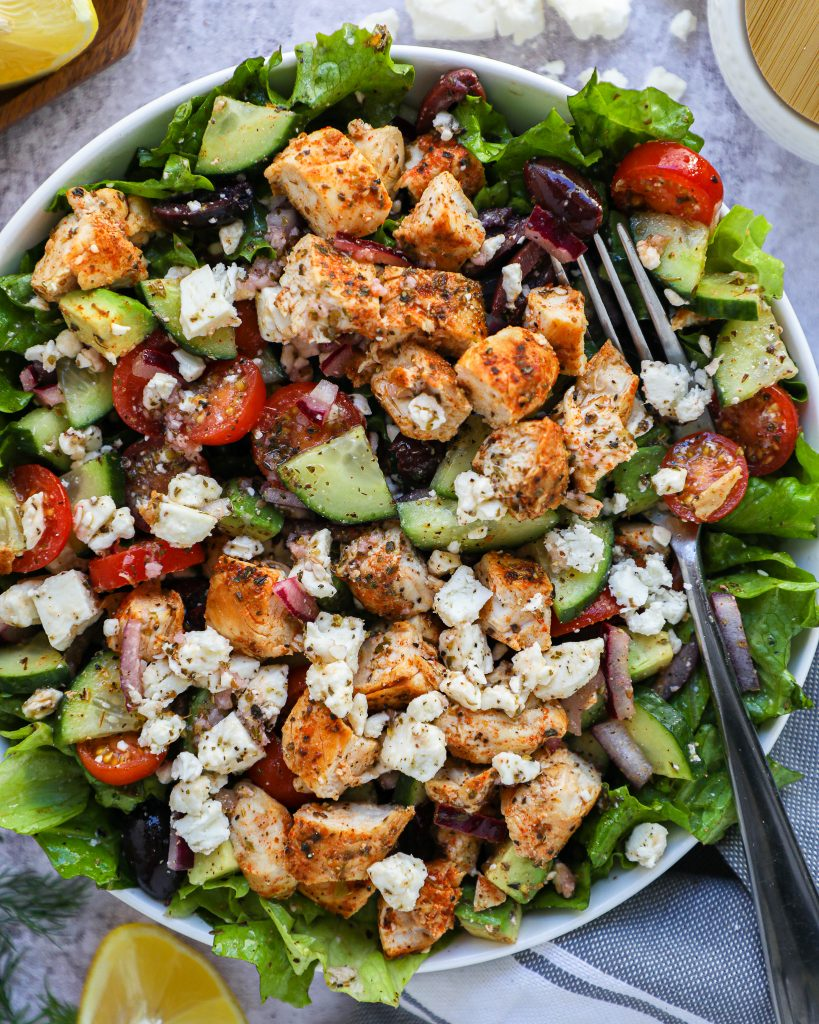 A healthier Greek salad recipe made with chopped lettuce, chicken, grape tomates, cucumber, onion, kalamata olives, avocado and feta cheese and tossed in a tangy lemon-herb dressing!