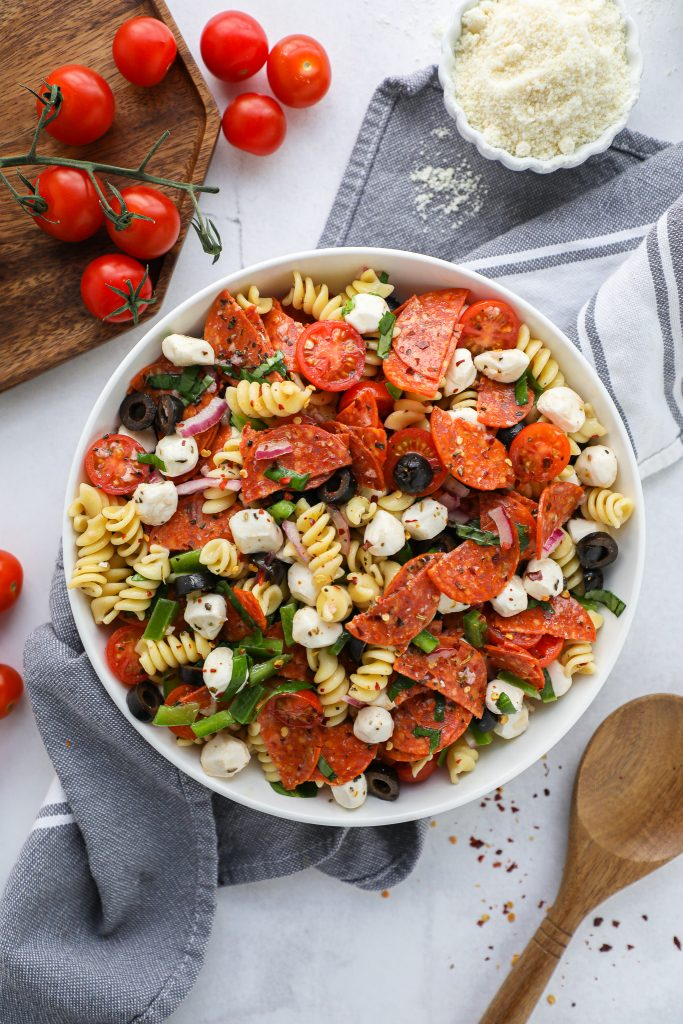 Pasta salad in a white bowl sprinkled with red pepper flakes surrounded by a wooden spoon and cherry tomatoes