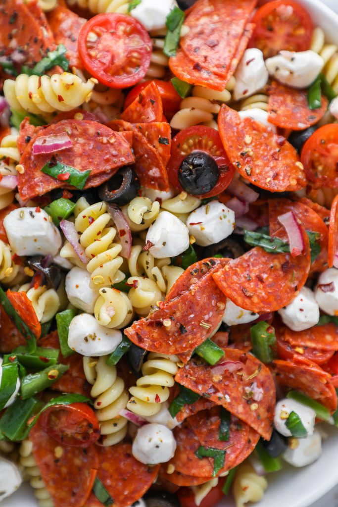 Close up of rotini pasta, mozzarella pearls, peperoni slices, chopped green pepper and red onion, sliced olives and tomaotes and fresh basil