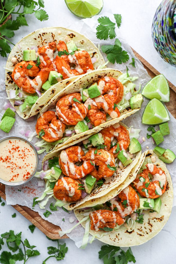 Shrimp tacos on a wooden board surrounded by lime wedges, diced avocado and chipotle lime sauce
