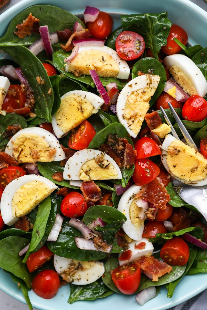 Spinach, hard boiled eggs, crispy bacon, tomatoes and red onon are all tossed in a tangy homemade red wine dressing! This is the best spinach salad you will ever make!