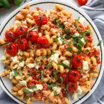 This lightened up version of baked feta pasta is so rich and delicious you'll keep making it againa and again! It's made with less oil, a fresh squeeze of lemon and a few other added spices too!