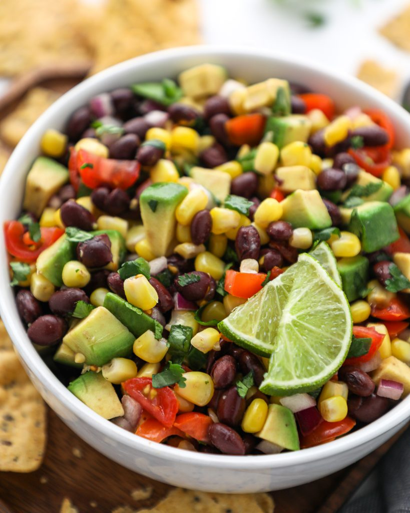 A healthy salsa recipe made with black beans, corn, avocado, lime and cilantro! It's the perfect game day and party appetizer!