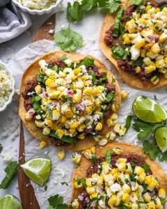 Easy homemade black bean tostadas topped with shredded lettuce and mexican corn salsa! They're quick, easy and so much fun to make!