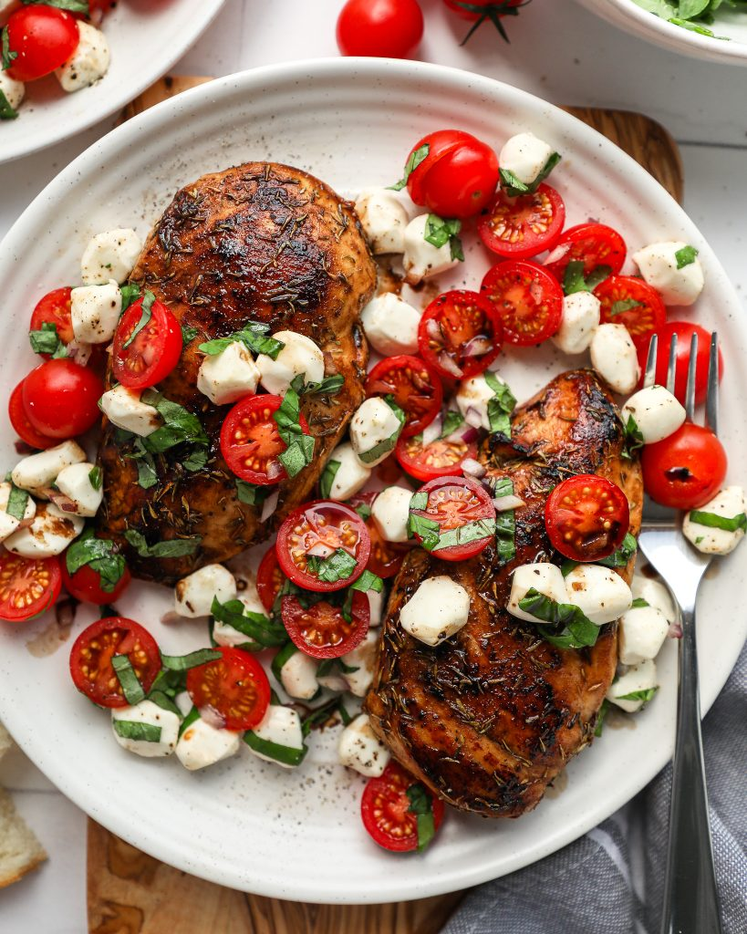 Boneless skinless balsamic chicken breast that's been baked in the oven and topped with caprese salsa sitting on a white plate