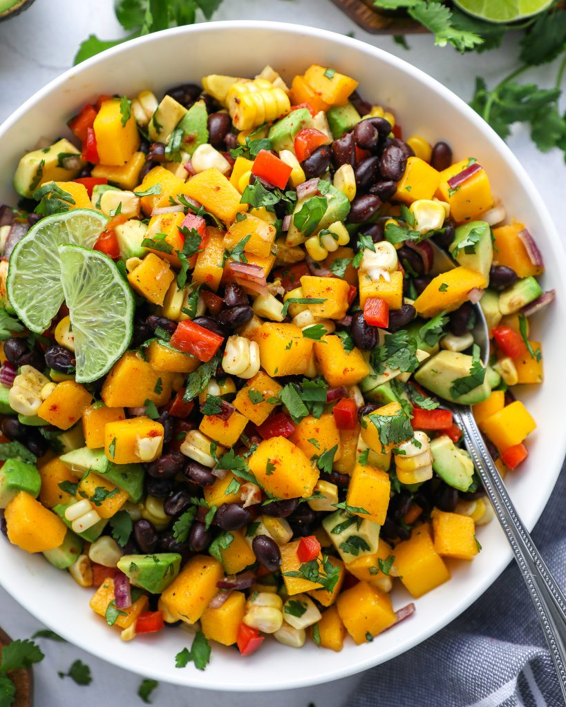 An easy and refreshing salad made with black beans, mangos, avocado, corn, red pepper, Mexican spices, cilantro and lots of lime juice! It's the perfect side dish to serve for a crowd!
