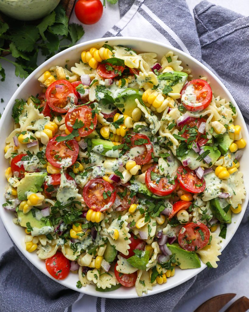 A quick and easy pasta salad recipe that's made with bow tie pasta, fresh corn, tomatoes, red onion and avocado and all tossed in an easy cilantro lime dressing!