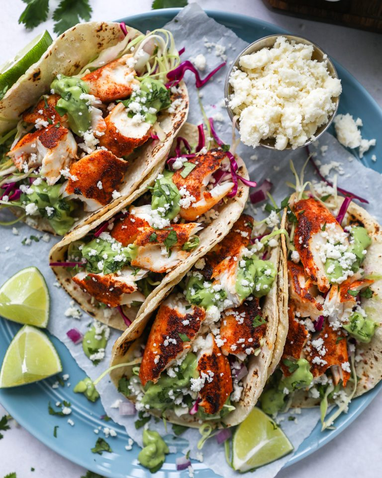Charred corn tortillas stuffed with chipotle rubbed tilapia, cabbage and avocado sauce sitting on a blue plate with cotija cheese on the side