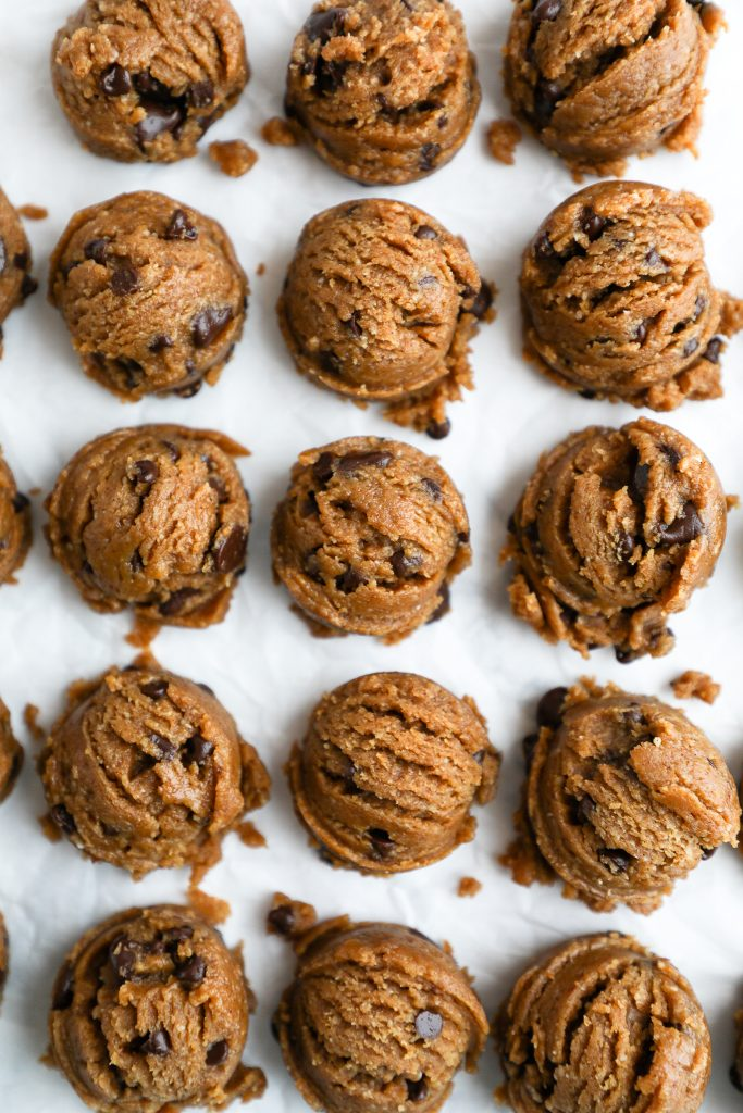 Scooped balls of edible cookie dough sitting in a row on white parchment paper
