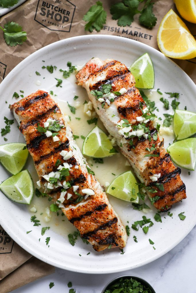 Cilantro lime halibut on a white plate with lime and lemon wedges