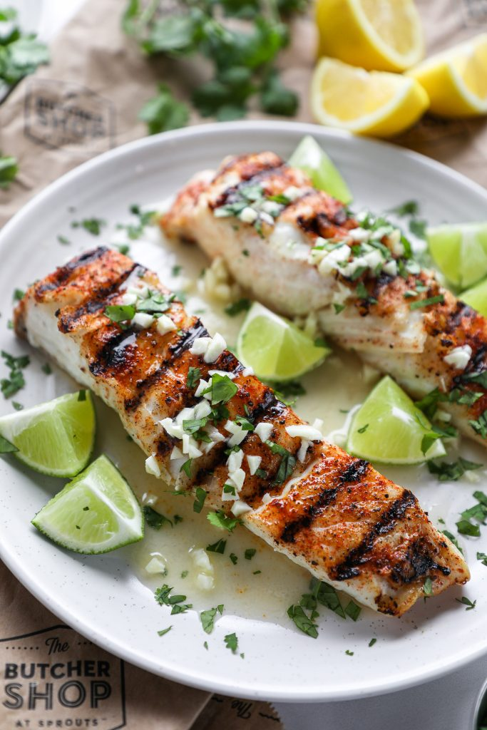 Close up of a grilled halibut fillet drizzled in cilantro garlic lime butter