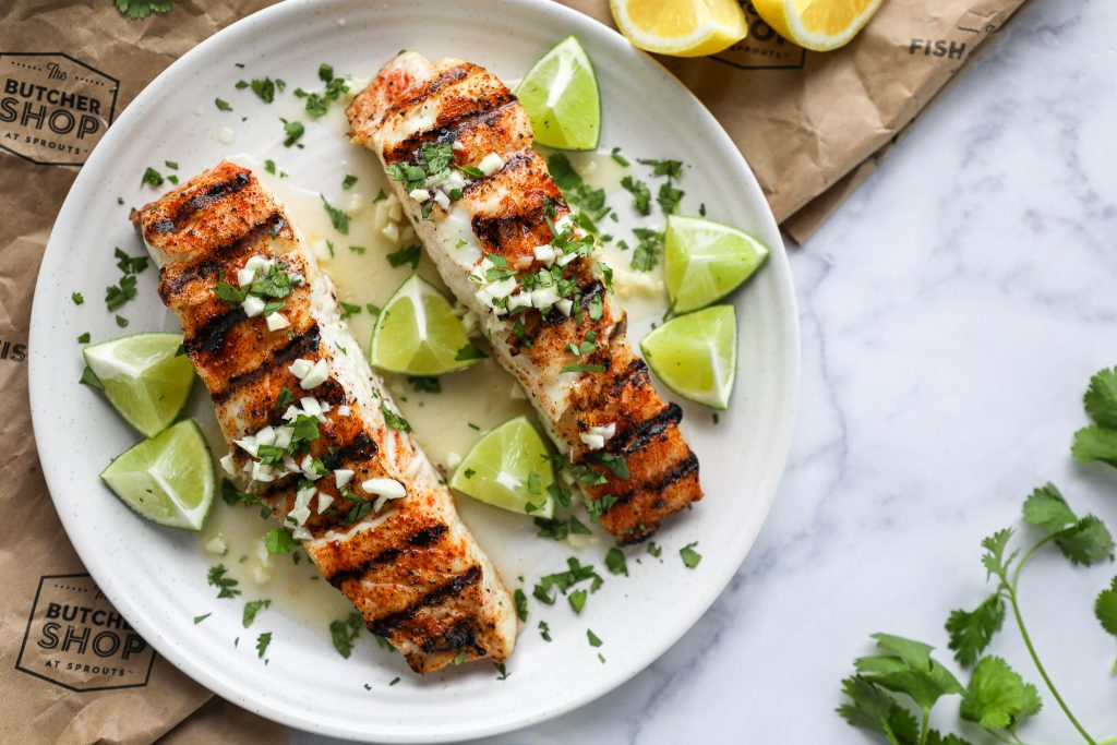 2 grilled halibut fillets on a white plate sitting on a marble counter surrounded by lemon wedges, lime wedges and fresh cilantro