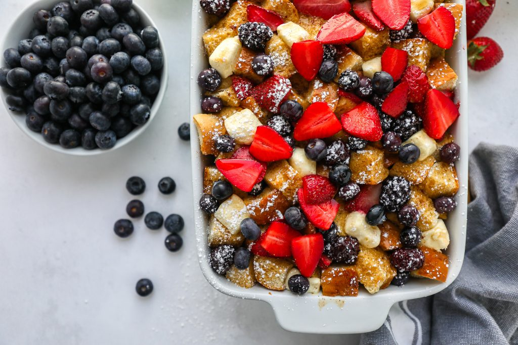 French toast casserole sprinkled with powdered sugar and topped with berries sitting next to a while bowl filled with blueberries