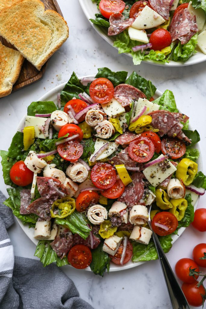 A plateful of healthy Italian sub salad dressed in a red wine vinaigrette and served with garlic bread