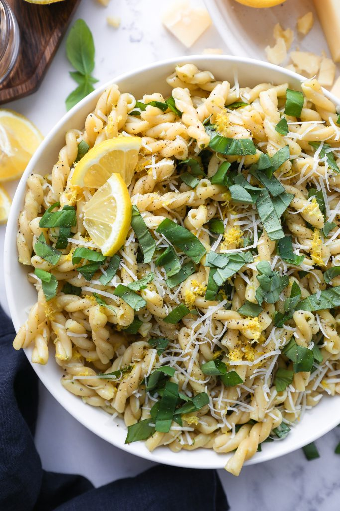 Close photo of pasta salad made with lemon basil and parmesan cheese in a white bowl sitting next to a dark blue linen napkin
