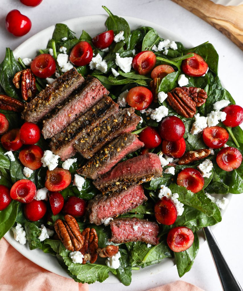 A salad made with spinach, fresh cherries, goat cheese, toasted pecans and seared steak sitting on a white plate with a silver fork sticking out of it