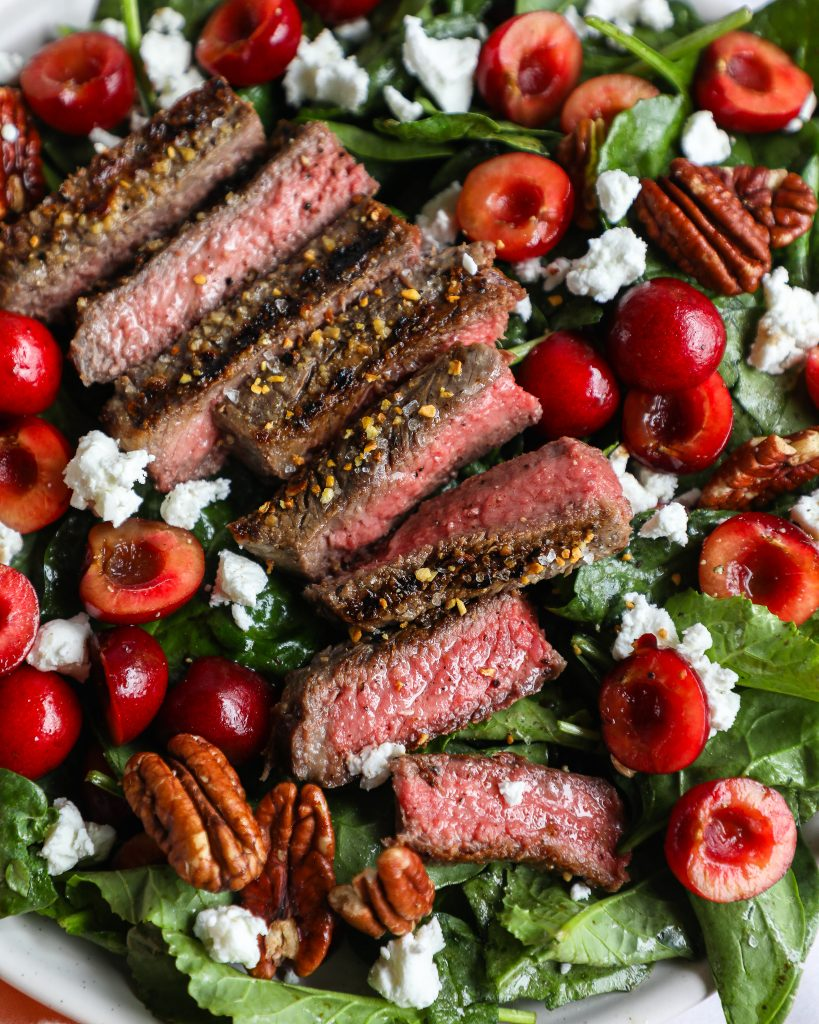 Close up of steak and cherry salad tossed with a balsamic vinaigrette