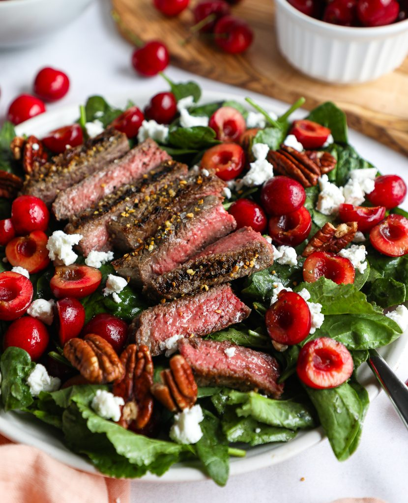 Steak and cherry salad with goat cheese and pecans sitting on a white plate next to a bowl of red cherries