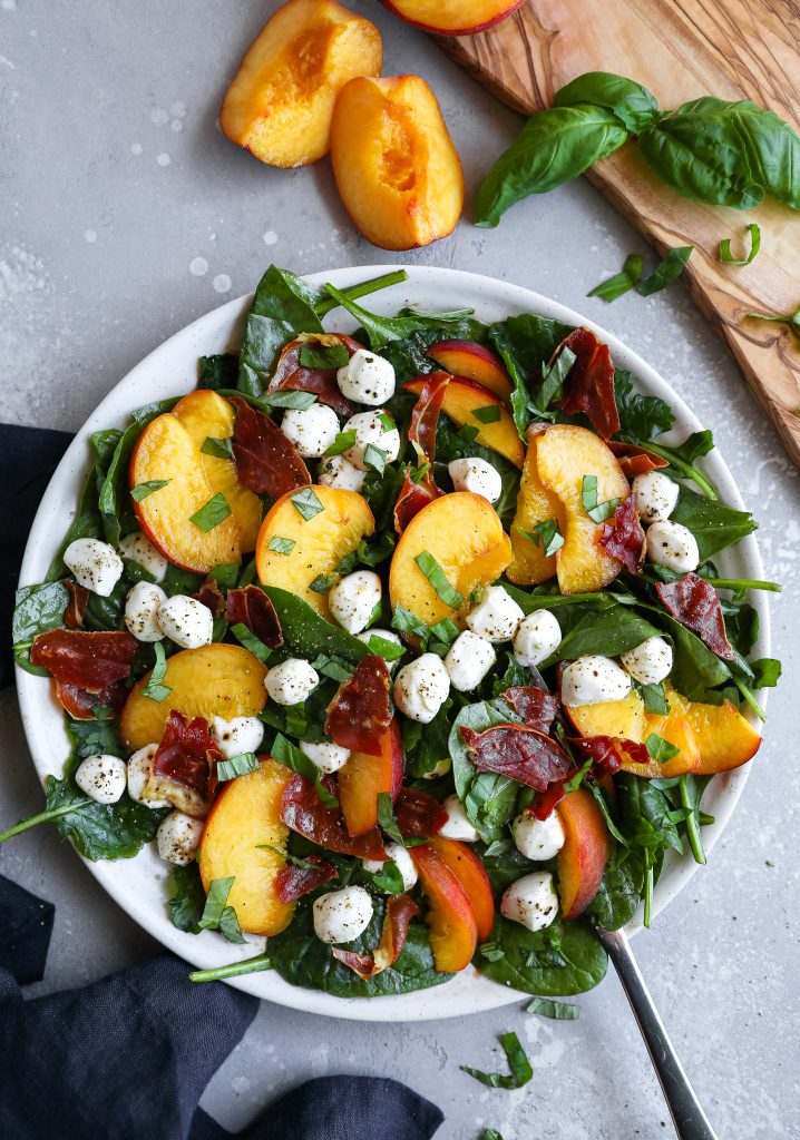 A summer salad made with sliced peaches, mozzarella balls, sliced fresh basil and baked crispy prosciutto sitting on a white plate with a silver fork digging into it
