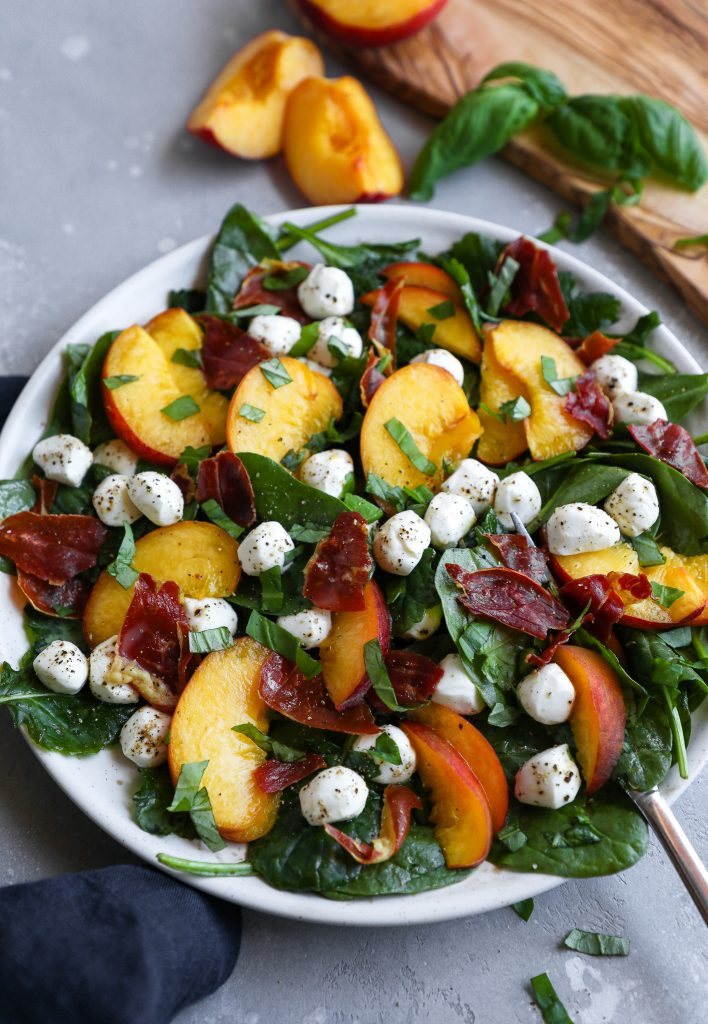 A side angle of peach, mozzarella and prosciutto salad on a plate sitting next to a blue linen napkin