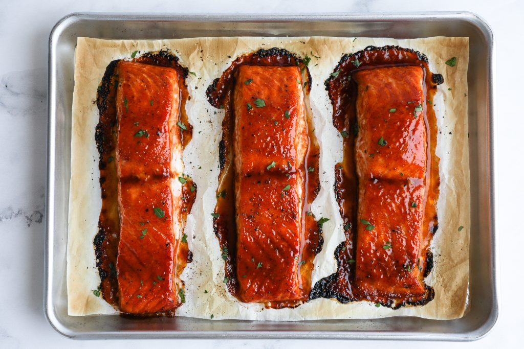 3 maple bbq salmon fillets fresh from the oven sitting on a baking pan lined with parchment paper