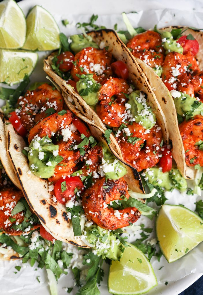Close up photo of shrimp tacos stuffed with a cabbage and lettuce blend, cotija cheese and avocado sauce