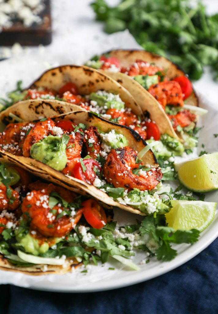 4 chili lime shrimp tacos made with corn tortillas sitting on a white plate surrounded by a blue napkin, cilantro and crumbled cotija cheese