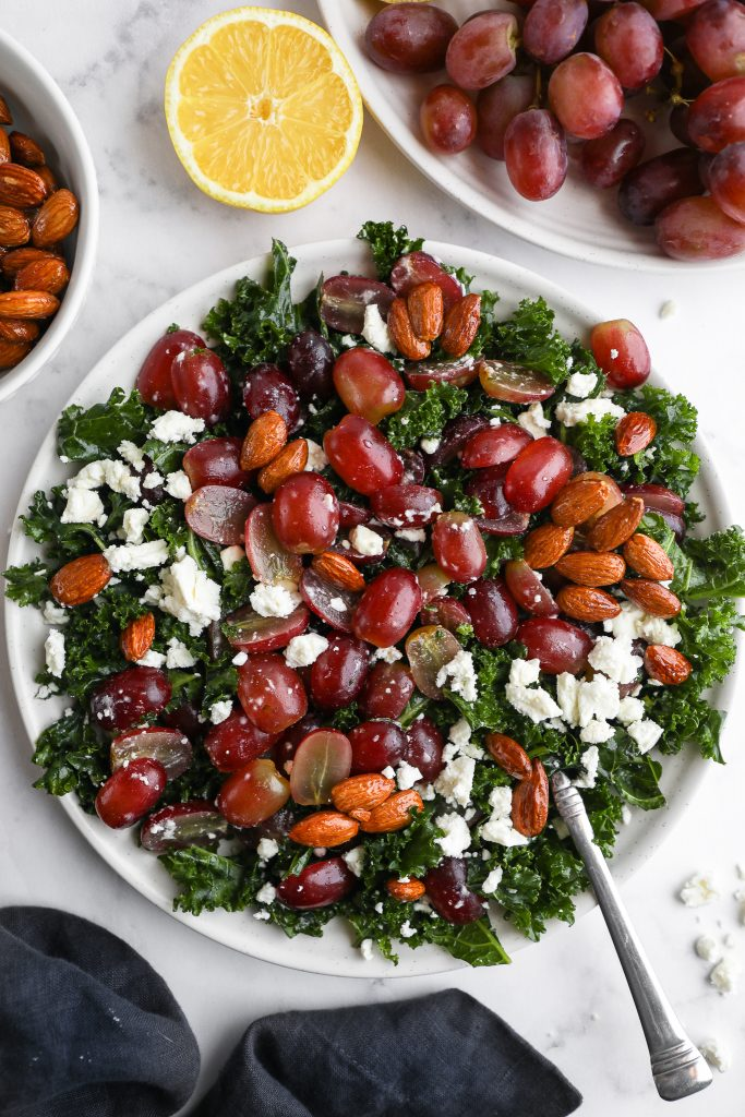 A kale salad made with grapes, feta cheese and candied almonds on a white plate surrounded by a blue napkin, a plate with grapes on the vine and a lemon slice