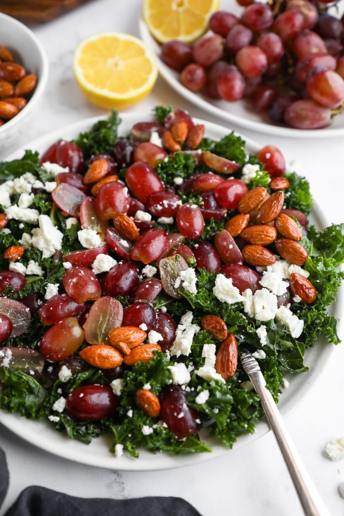 Side angle of a kale salad topped with red grapes, crumbled feta and candied almonds drizzled in a lemon-dijon vinaigrette