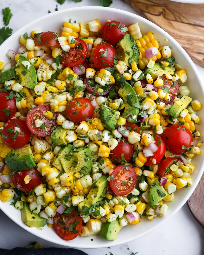 A summer salad made with fresh corn, cherry tomatoes, red onion, diced avocado, cilantro and lime juice tossed in a large white bowl