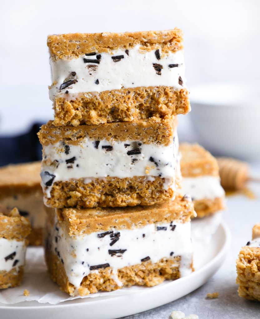 3 peanut butter rice krispie ice cream sandwiches stacked on top of each other sitting on a white plate next to a honey dipper