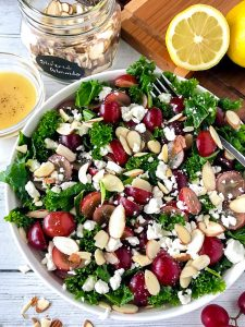 Kale salad with grapes, feta, and sliced almonds in a white bowl sitting next to a small clear bowl of lemon mustard dressing