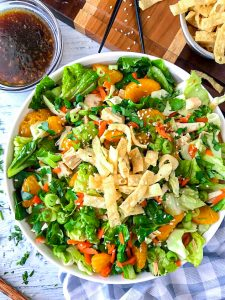 Asian chicken salad in a white bowl sitting next to a wooden board with dressing in a small clear bowl off to the side