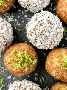 Two key lime pie protein balls on a gray plate. One is covered in coconut and the other is topped with lime zest.