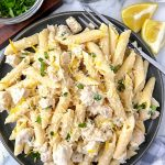 Penne pasta in a lemon basil cream sauce with chicken and parmesan cheese on a dark gray plate sitting next to lemon wedges and small bowls of basil and Parmesan cheese