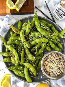 Everything seasoned edamame made with lemons and garlic sitting on a gray plate next to dark brown chopsticks