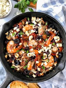 A Greek inspired one skillet dish made with shrimp, tomatoes, onions, artichokes, olives and feta cheese and is sprinkled with fresh parsley