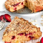 A slice of plum coffee cake with a streusel topping sitting on a piece of parchment paper with the rest of the cake sitting in the background