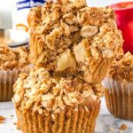 2 apple muffins with peanut butter streusel stacked on top of each other with an apple and peanut butter jar in the background. They're healthy and delicious!
