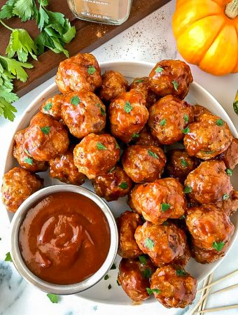 Pumpkin bbq meatballs sitting on a white plate next to a homemade sauce made of barbeque sauce, canned pumpkin and cinnamon.